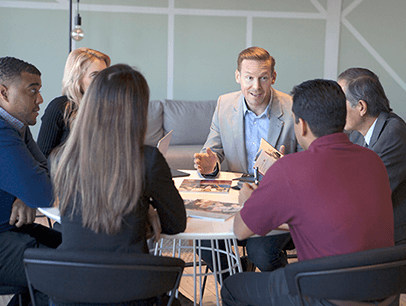 Men and women sitting around a conference table talking