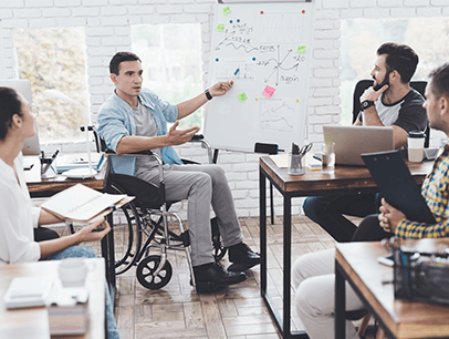 Man in wheelchair presenting to three other people at work