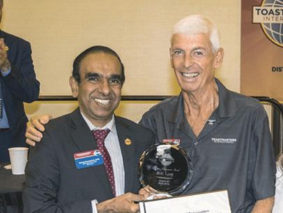 Toastmasters International President Deepak Menon awards member Bob Turel a certificate