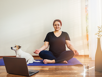Woman watching laptop and posing on purple yoga mat with a dog