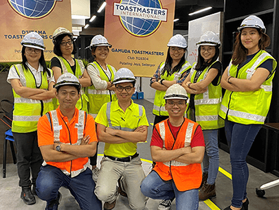 Group of Toastmasters wearing hard hats and yellow and orange vests pose in front of banners