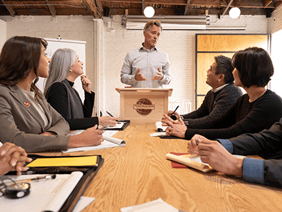 Group of people sitting around conference table while man speaks at a lectern