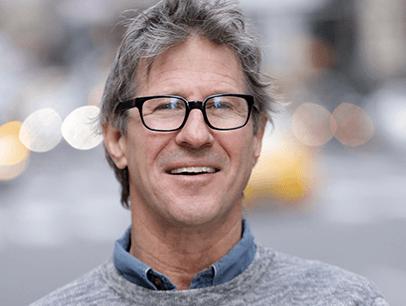 John Bowe posing in gray sweater