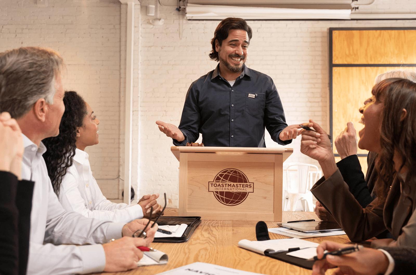 Man standing at lectern telling joke to people around table