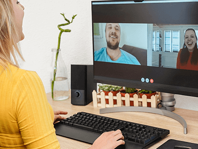Woman in yellow shirt talking to man and woman on her computer