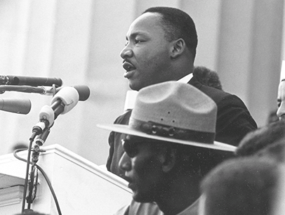 Martin Luther King Jr. speaking into microphone