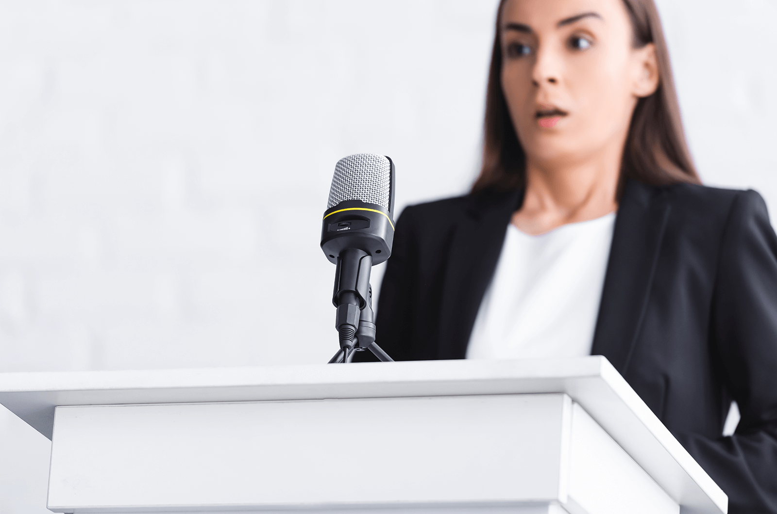 Woman standing at lectern looking scared