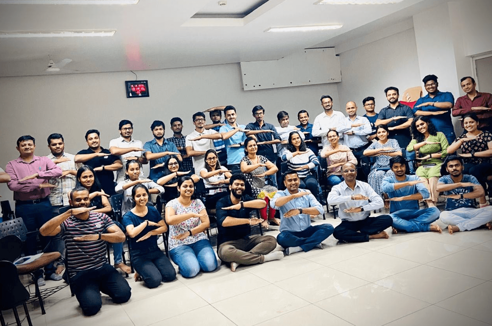 Group of Toastmasters in India posing with arms making equal signs