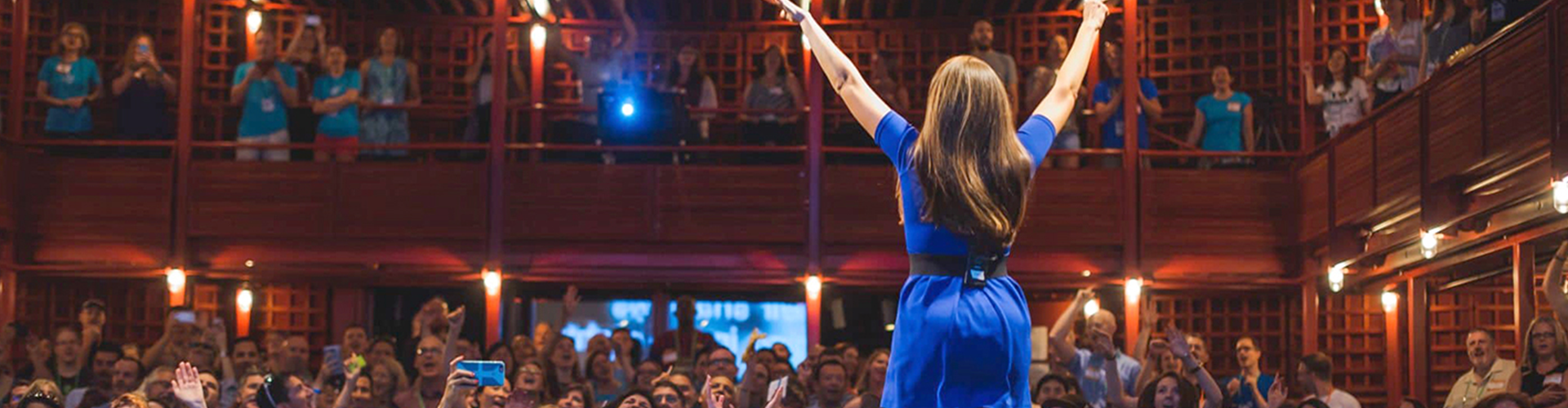 Woman in blue dress onstage with her hands up