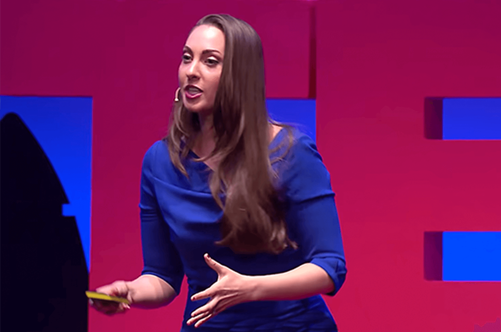 Woman in blue dress speaking onstage.