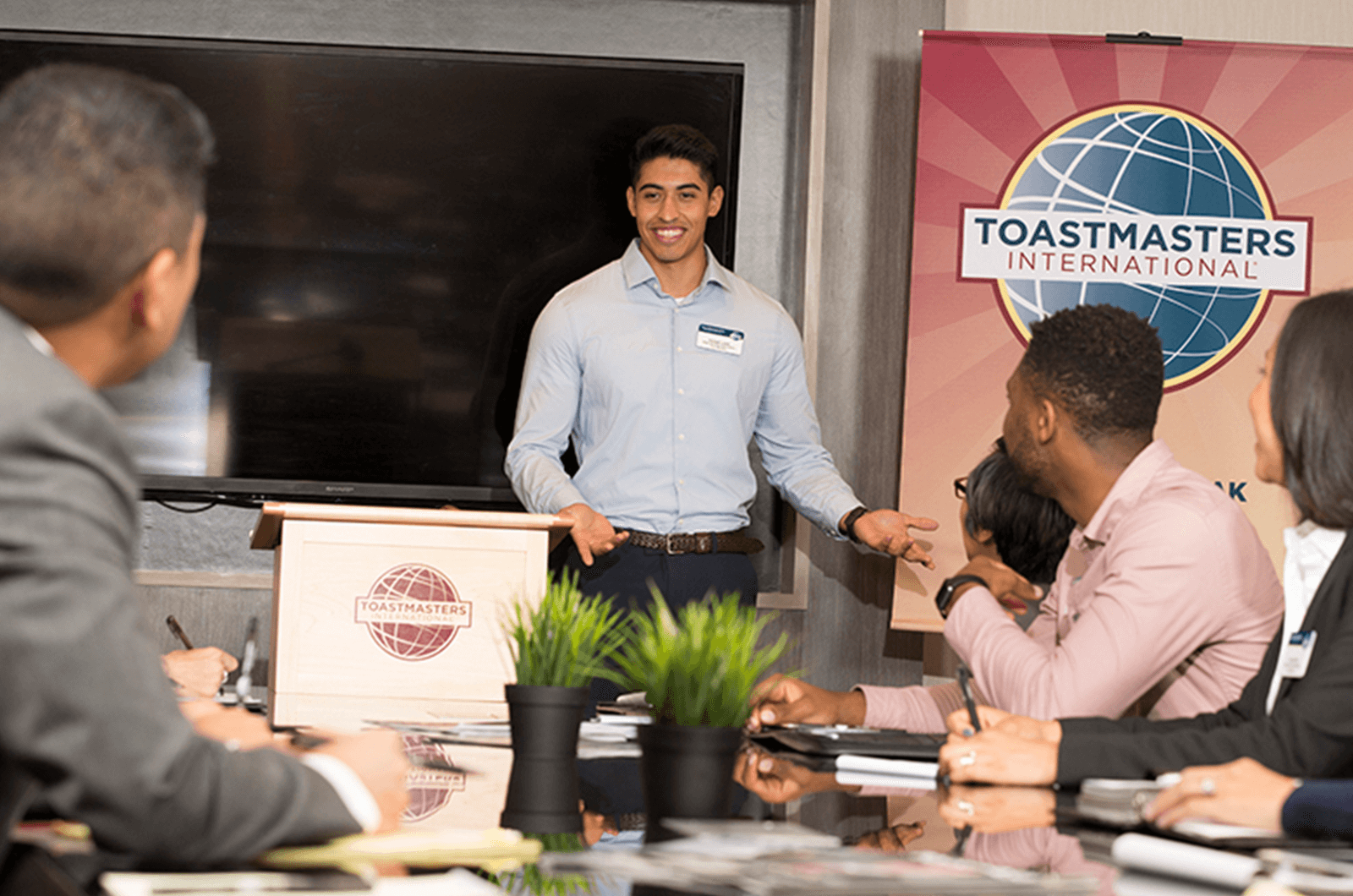 Man standing at lectern speaking at Toastmasters meeting