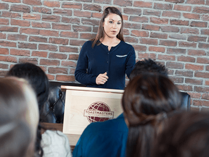 Woman in blue sweater speaking to group from lectern
