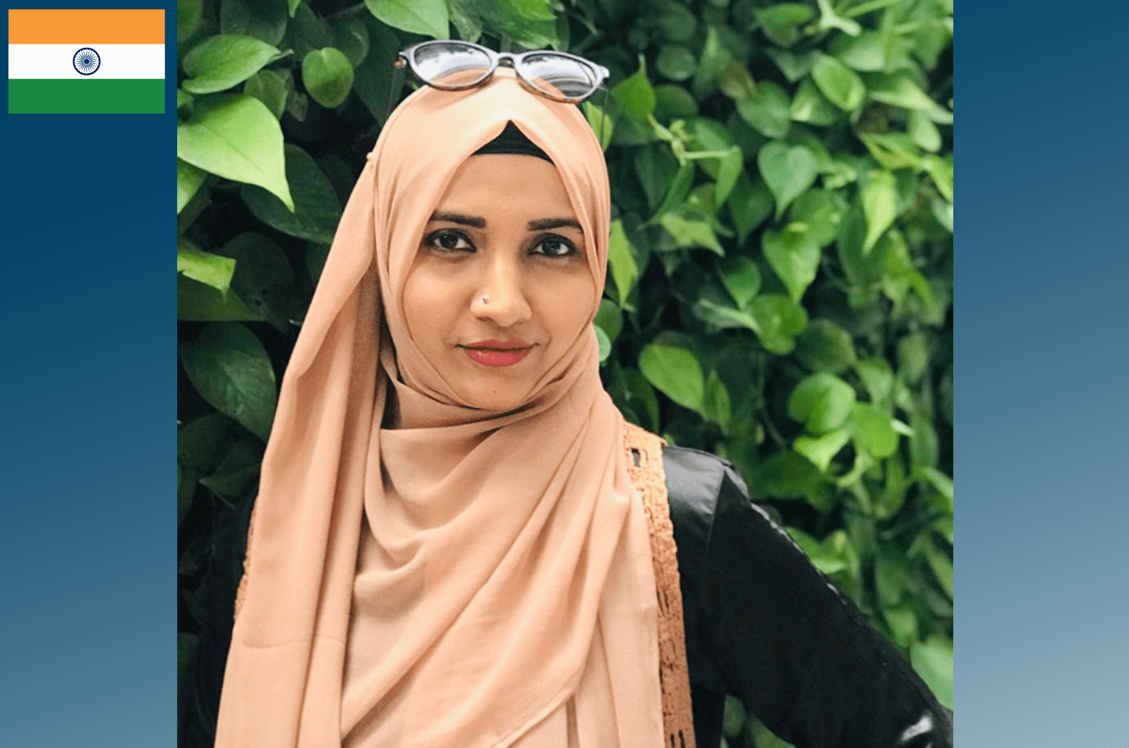 Woman wearing peach-colored hijab with tree in background