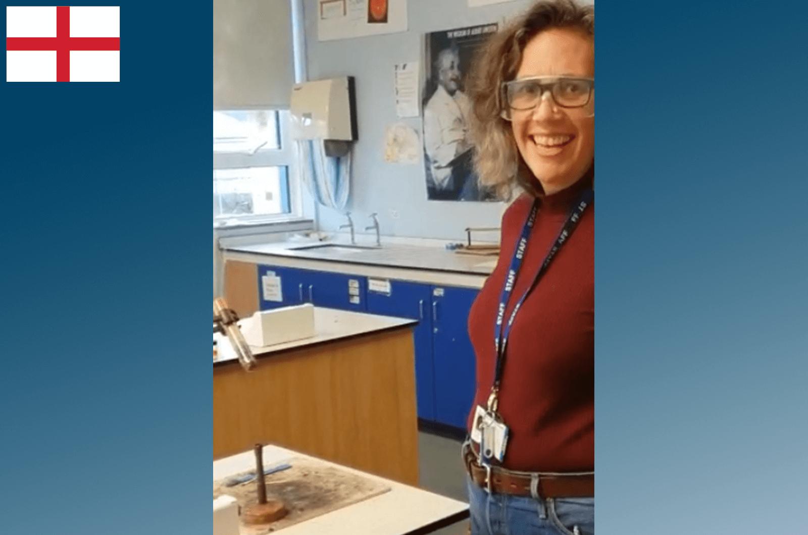 Woman wearing lanyard and smiling while teaching at school
