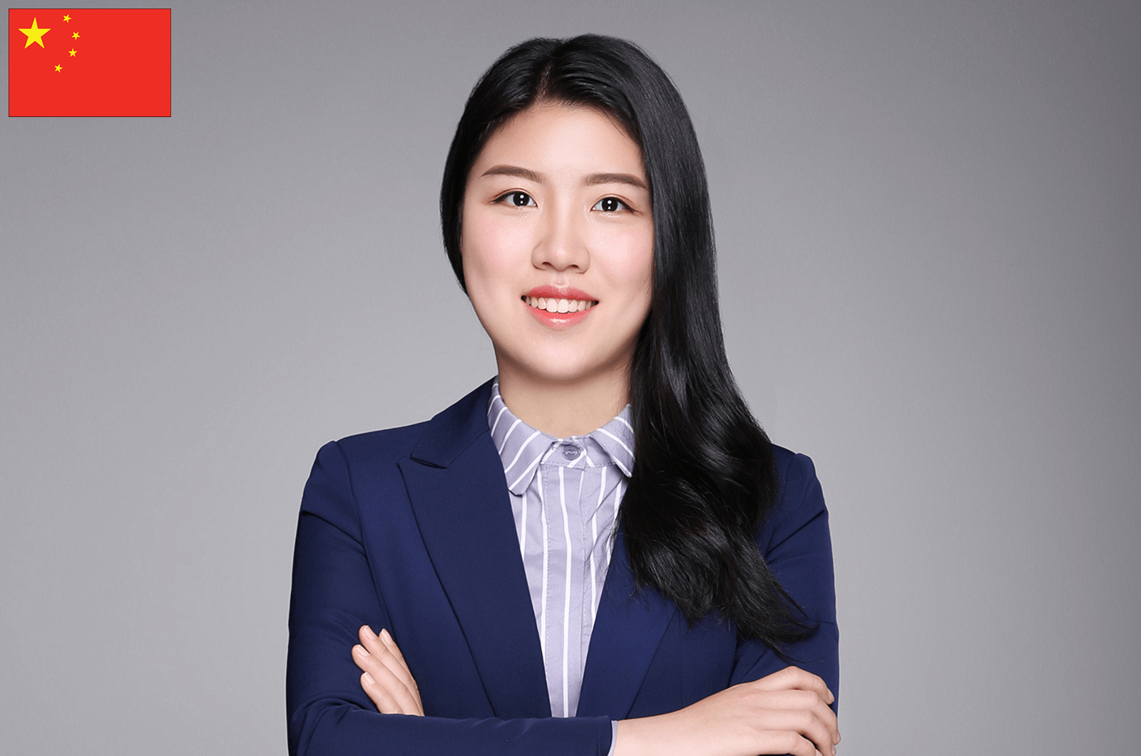 Julia Gu in suit jacket crossing arms and smiling