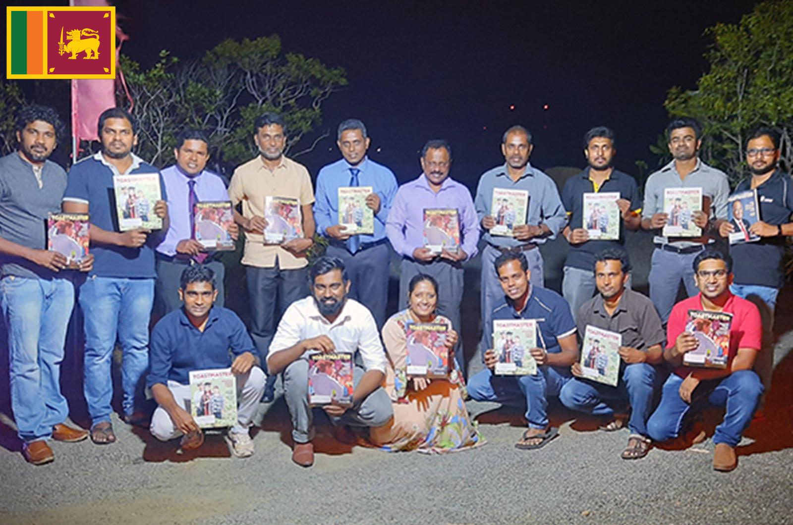 People standing outdoors at night holding Toastmaster magazines