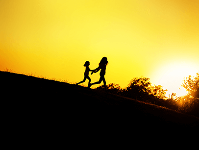 Silhouette of two kids running on hill while sun sets