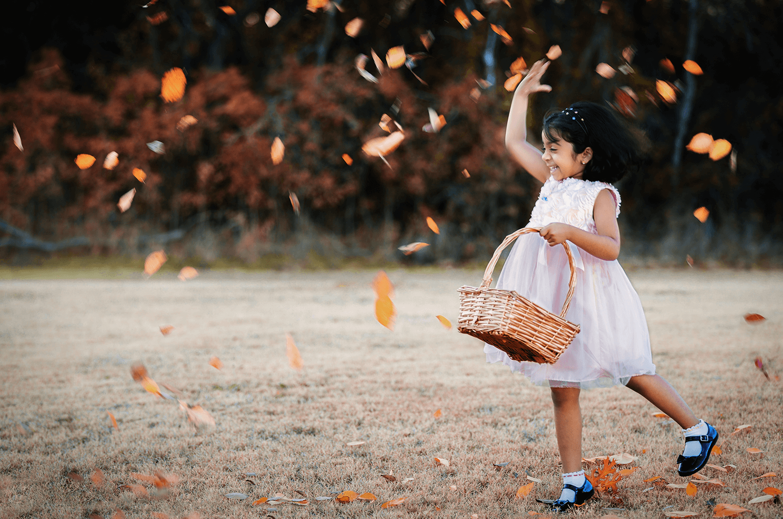 Little girl holding basket and throwing leaves in the air