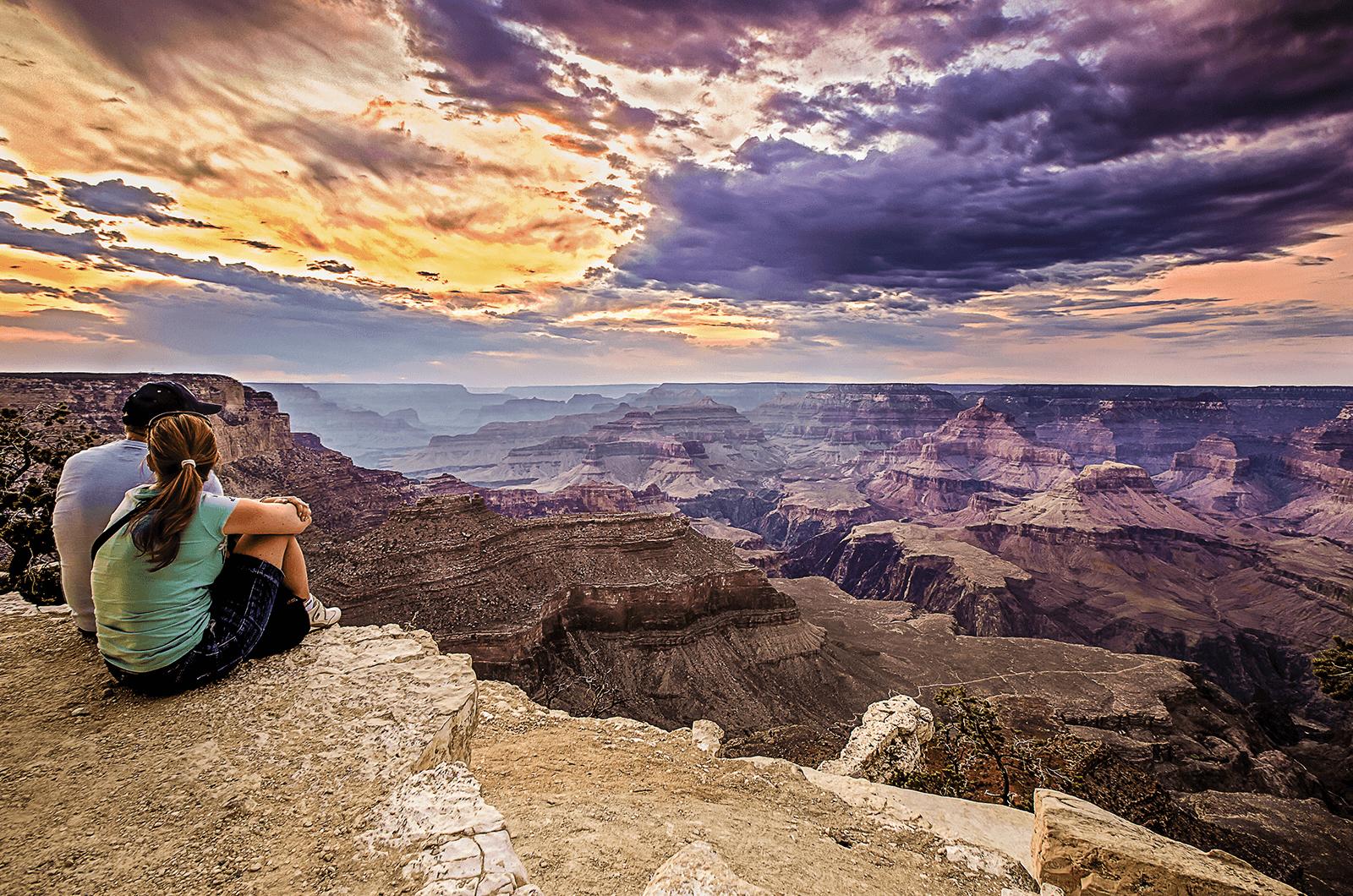 Young man and woman looking at sky at Grand Canyon
