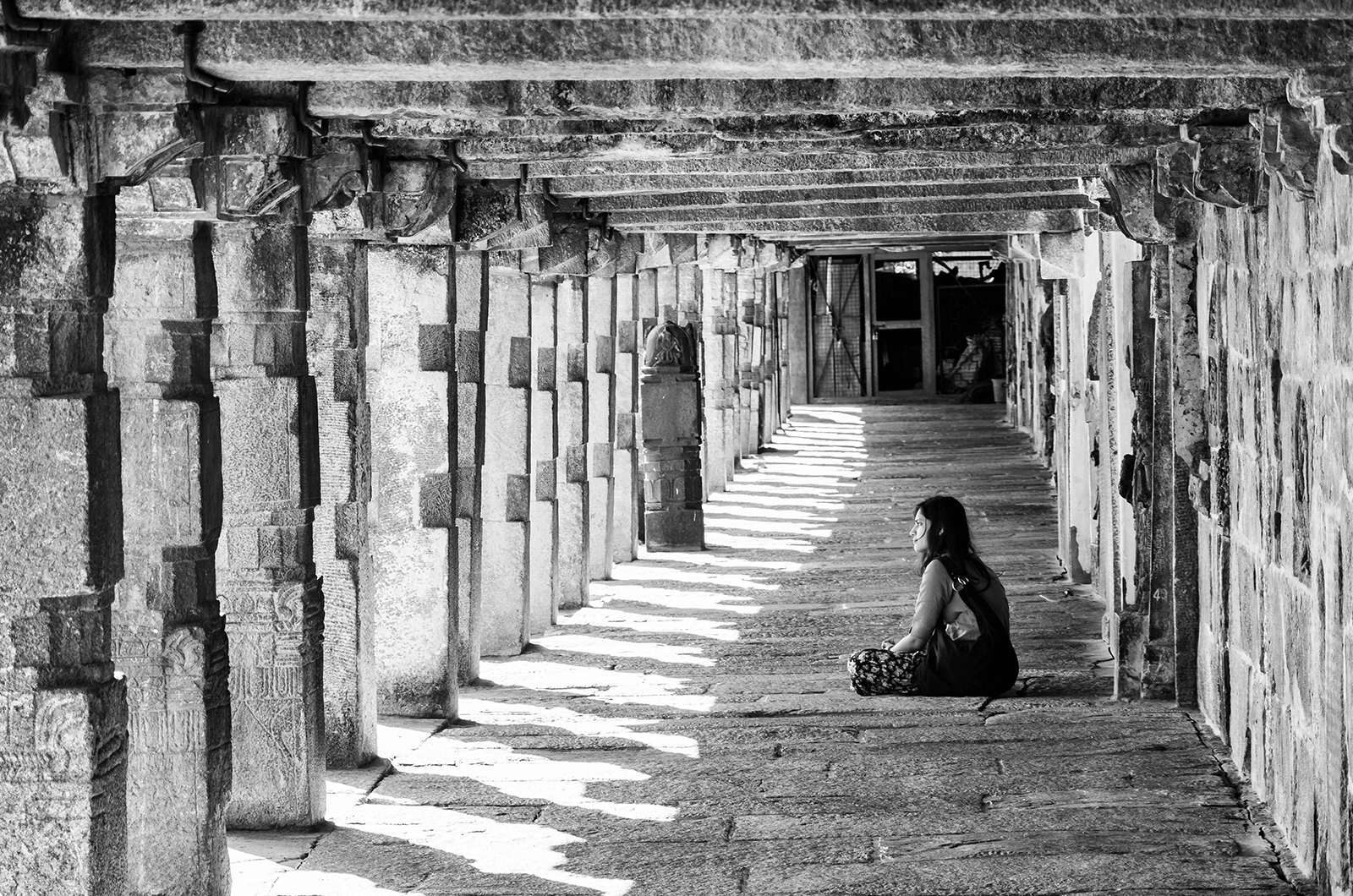 Black and white photo of woman sitting in temple in India