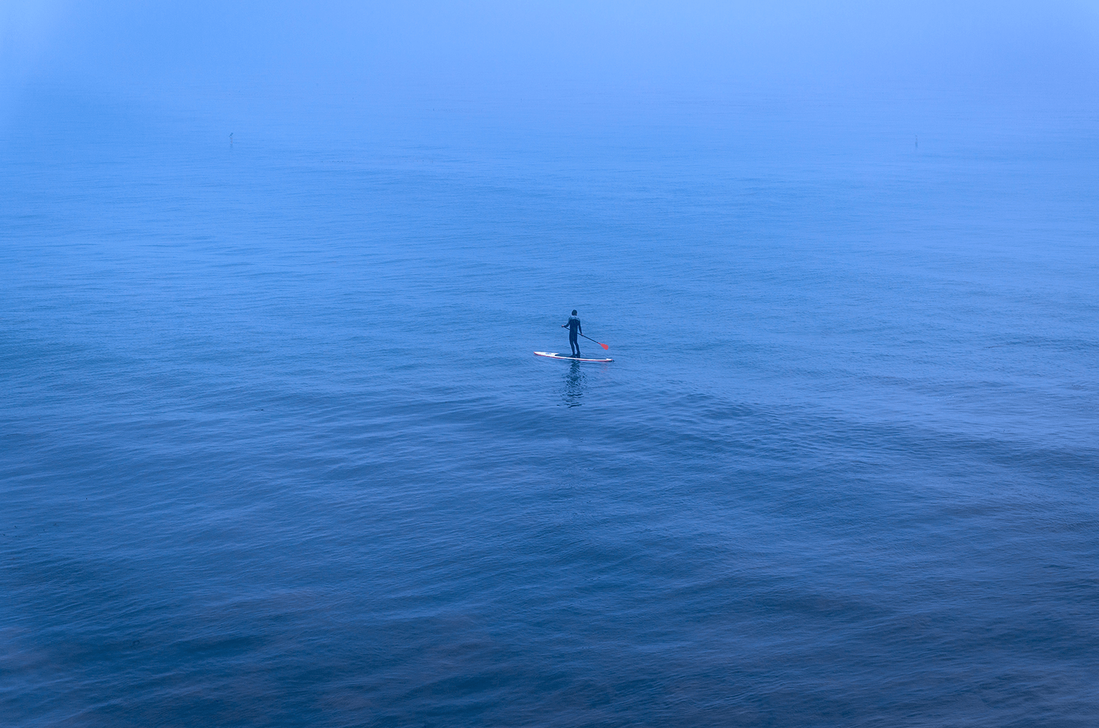 Man paddling a canoe in blue water