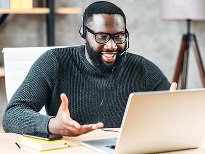Man wearing headset talking and looking at laptop