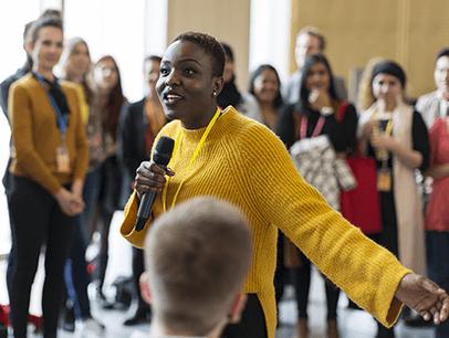 Woman in yellow sweater holding microphone speaking to audience