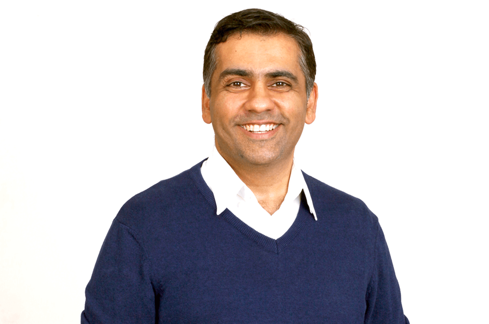 Man in blue sweater standing and smiling
