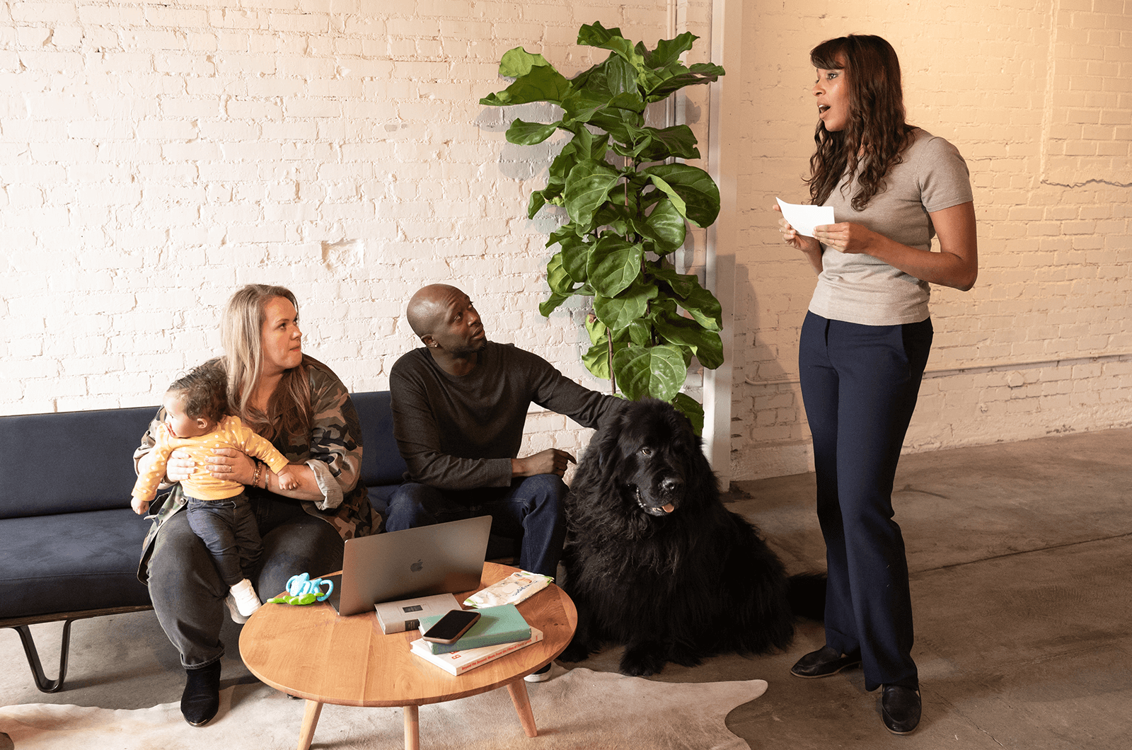 Woman holding note card speaking while woman with baby, a man, and dog watch from couch