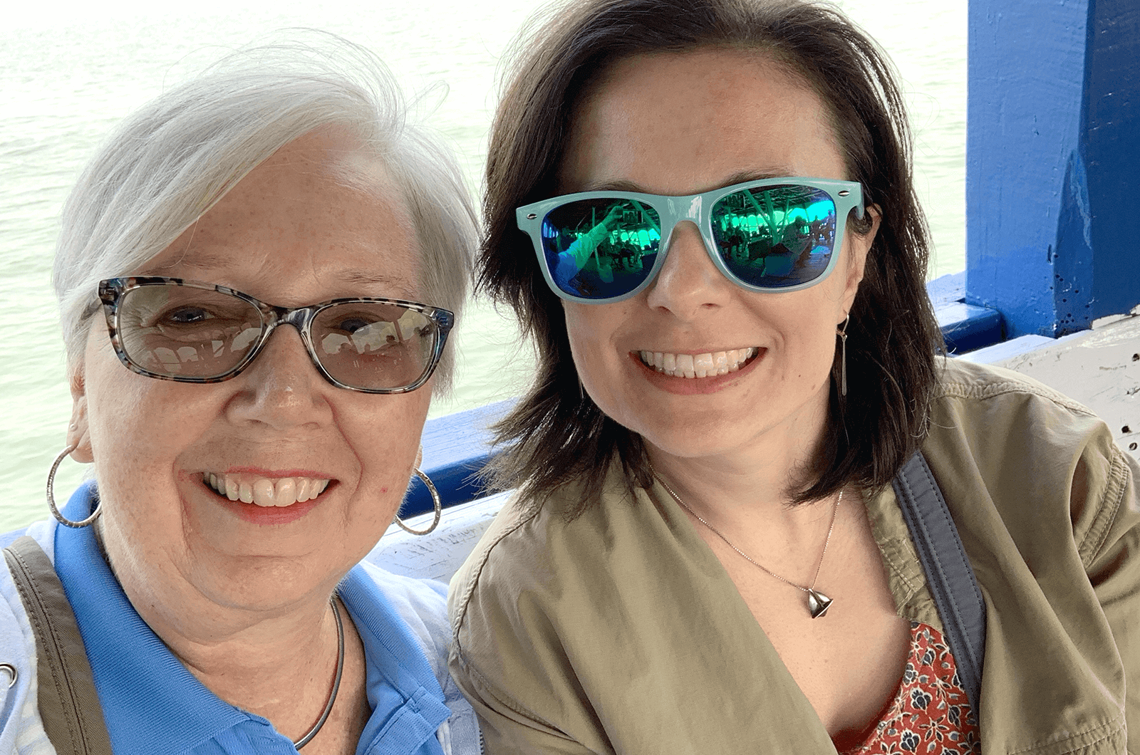 Two women posing and smiling wearing sunglasses