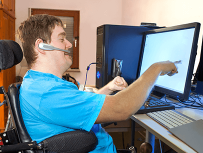Man wearing blue shirt sitting in wheelchair pointing at computer screen
