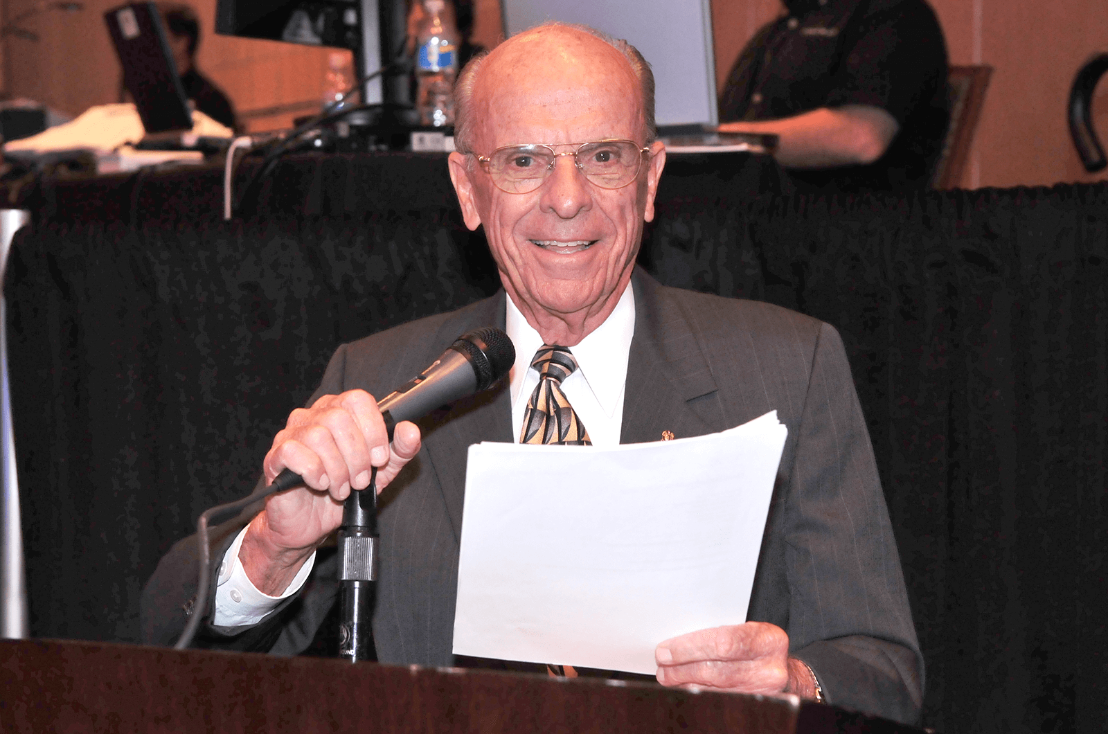 Don Ensch holding microphone and papers