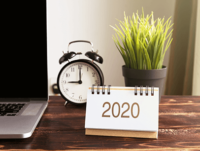Desk with laptop, clock, calendar, and plant