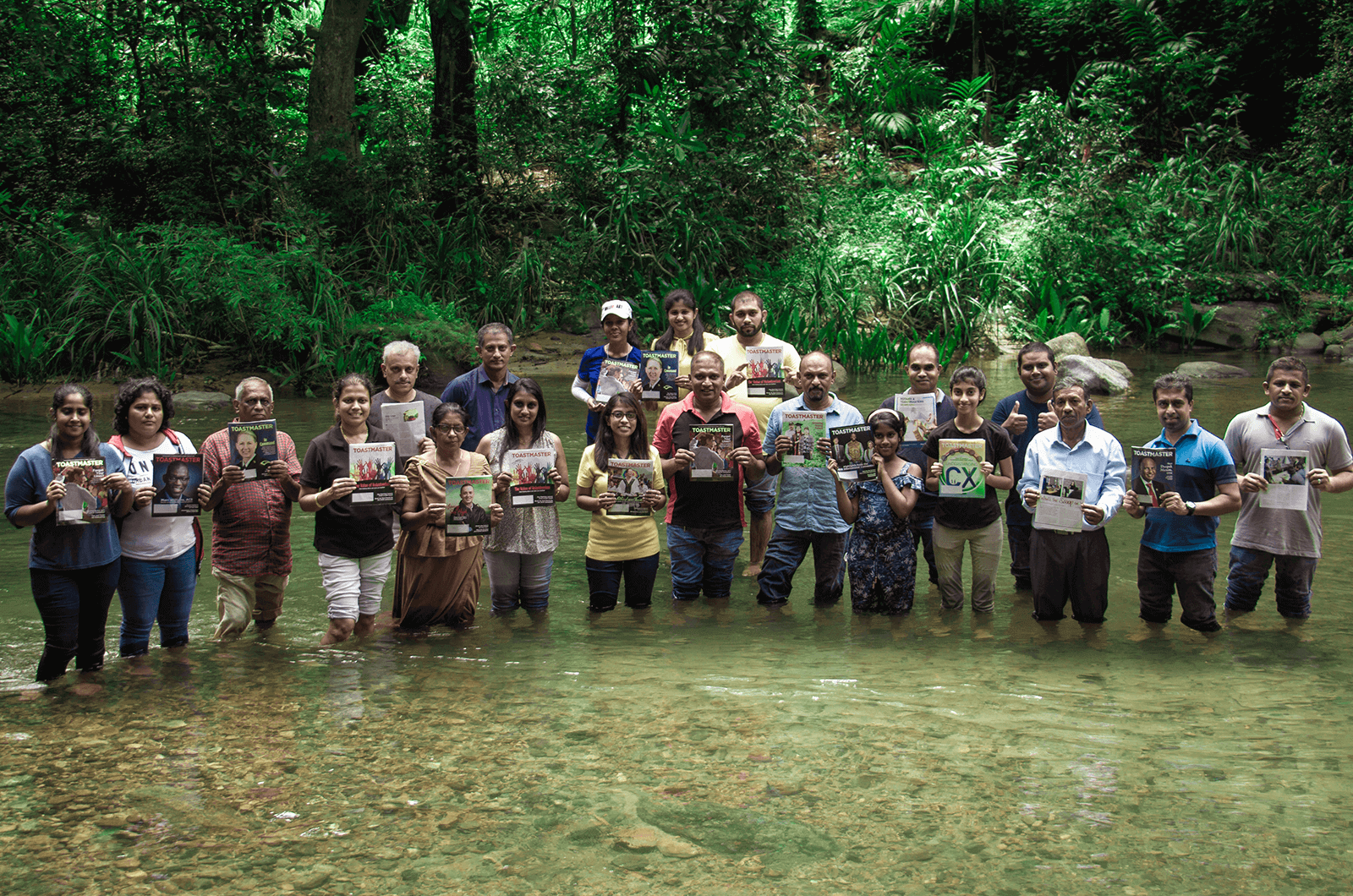 Group of people standing in a stream with Toastmaster magazines