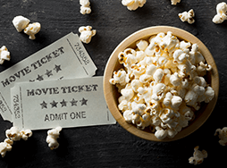 Two movie tickets and bowl of popcorn
