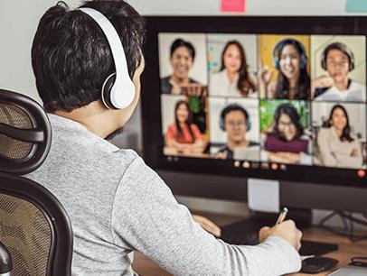 Man sitting at computer in virtual meeting wearing headphones