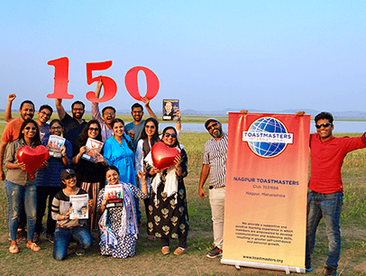 Group of people posing outdoors with banner and cut out numbers 150