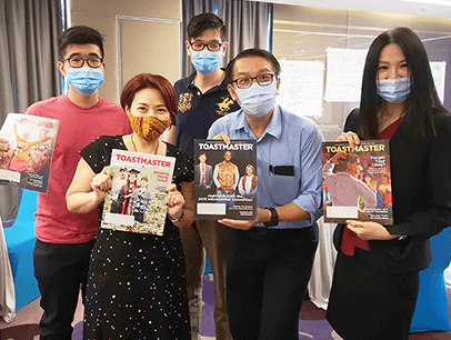 Group of people wearing medical masks holding magazines