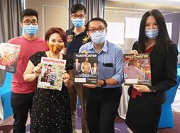 Group of people wearing medical masks holding magazines