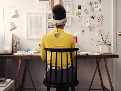 Woman in yellow sweater working at desk at home