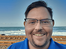 Man in glasses and blue shirt standing near ocean