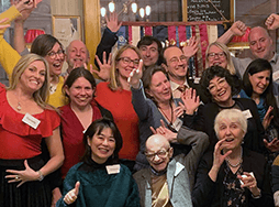 Group of people smiling and celebrating with hands up