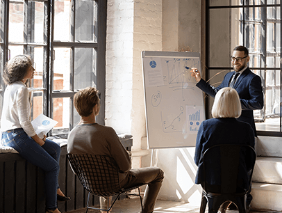 Man pointing to whiteboard for group of people