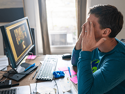 Man in front of computer with hands over eyes