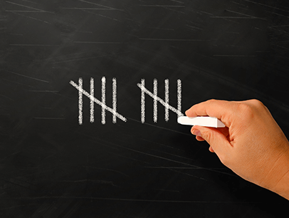 A hand writing numerals with chalk on blackboard