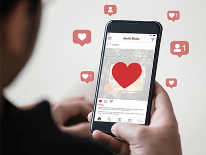 Social media hearts and thumbs up next to someone on smartphone