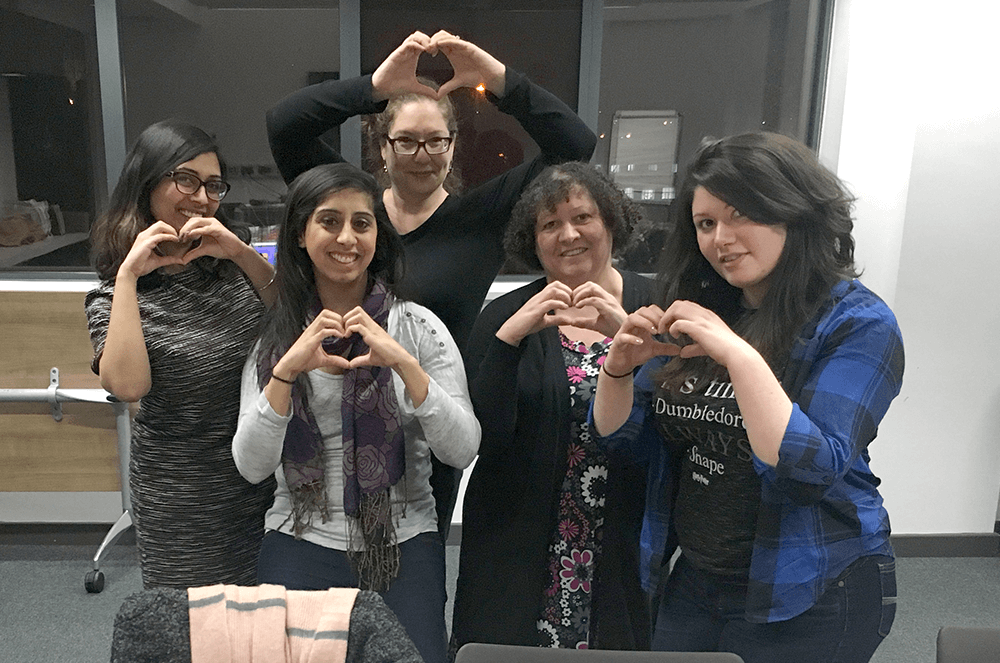 Tanya (far right) makes a heart shape with her hands with fellow members at a club meeting.