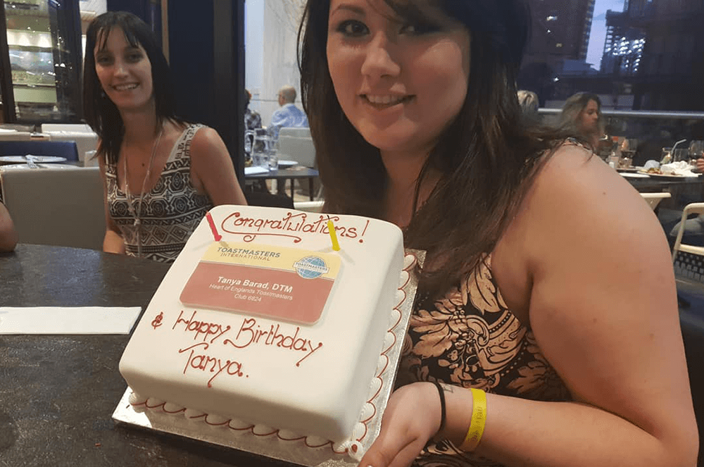 Tanya holds up a Toastmasters-themed cake for her birthday.