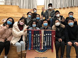 Group of people wearing masks and holding banner