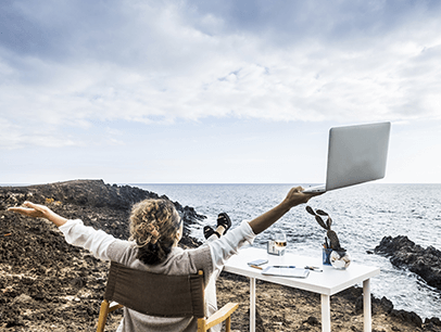 Woman holding laptop on beach looking at ocean